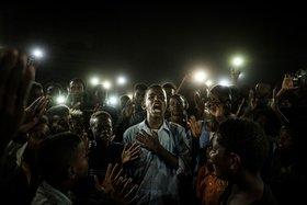 Pressebild des Jahres 2020 von Yasuyoshi Ciba: Das Fotozeigt einen jungen Mann im Sudan, der Protestpoesie und dabei von Mobiltelefonen beleuchtet wird.